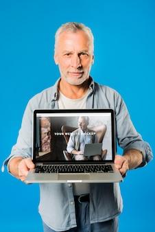 年配の男性人のラップトップモックアップを提示