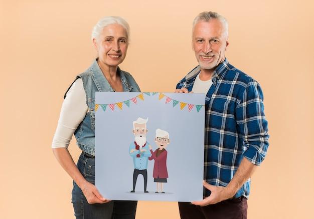 年配のカップルが祖父母の日にボードを提示