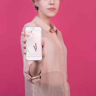 Молодая женщина, держащая смартфон макет