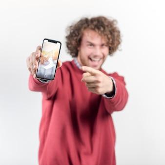 スマートフォンのモックアップを持ってうれしそうな男