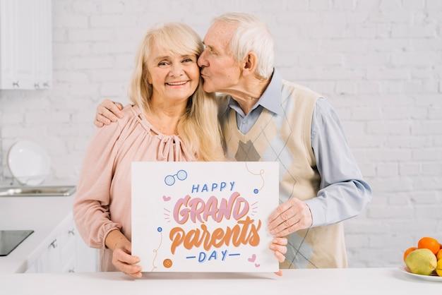 Бабушка и дедушка держат макет плаката