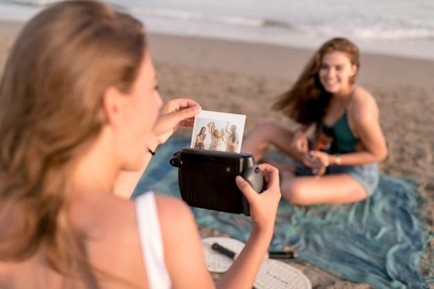 ビーチでインスタント写真を撮る女の子