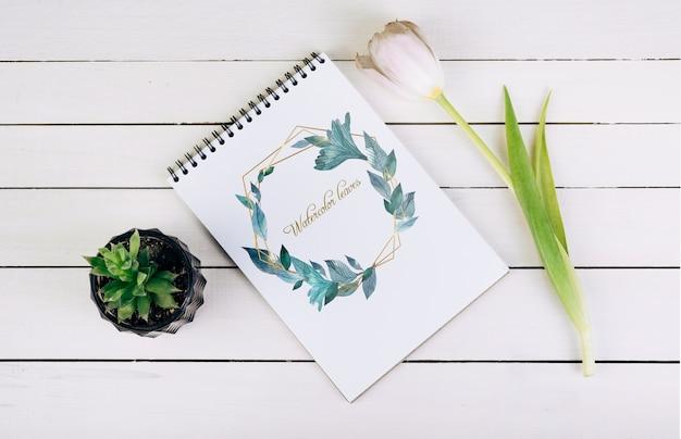 トップビューで装飾的な植物と春のノートブックモックアップ