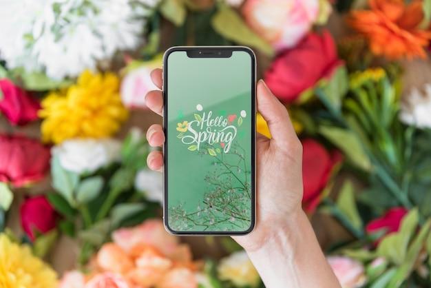 花の上のスマートフォンのモックアップを持っている手