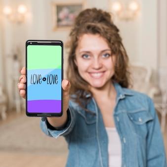 Улыбающаяся девушка, представляя смартфон макет