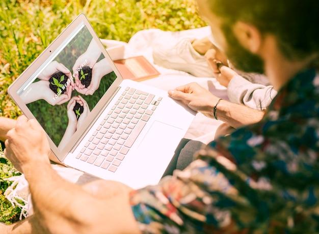 Человек, используя ноутбук макет в природе
