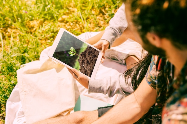 Человек с помощью планшета макет в природе