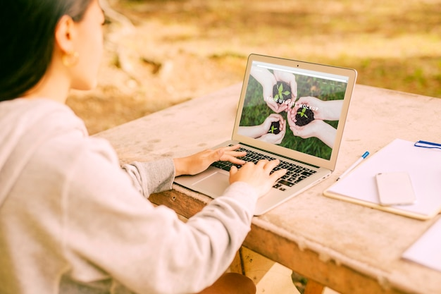 自然の中でラップトップモックアップをしている女の人