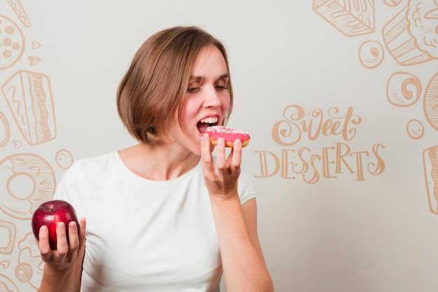 ドーナツとリンゴを食べる女