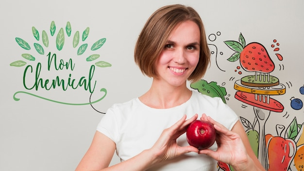 Улыбающаяся женщина, держащая яблоко
