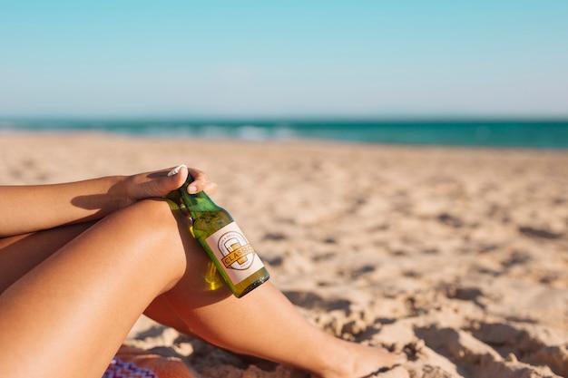 ビーチでビール瓶のモックアップを持つ女性
