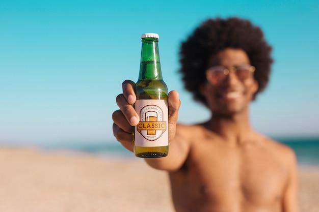ビーチでビール瓶のモックアップを持つ男