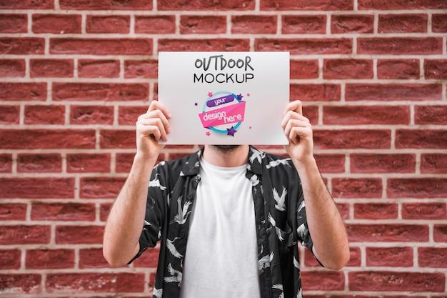 Человек, представляя плакат макет перед кирпичной стеной