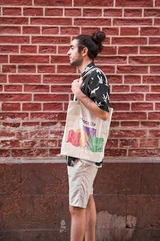 バッグのモックアップを持つ若者