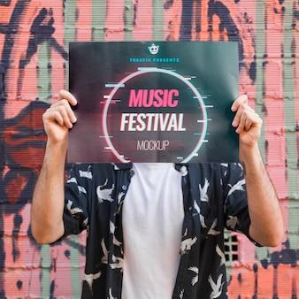 Человек, представляя плакат макет перед граффити стены
