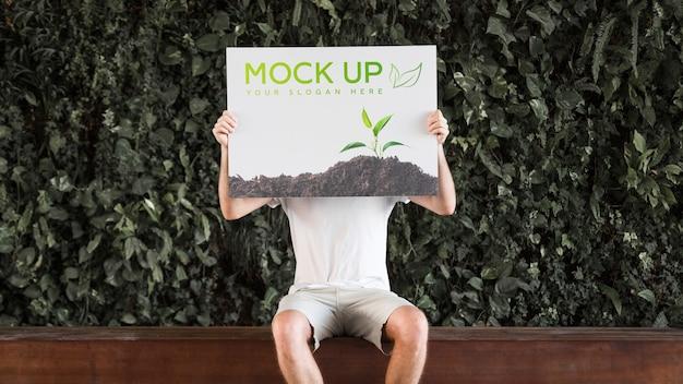 Человек, представляя плакат макет перед листьями