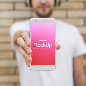 スマートフォンのモックアップを持つ若者
