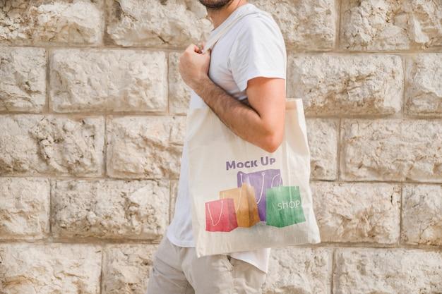 Молодой человек с макетом сумки