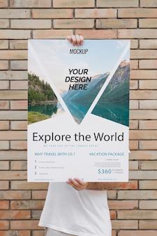 レンガの壁の前にポスターのモックアップを提示する男