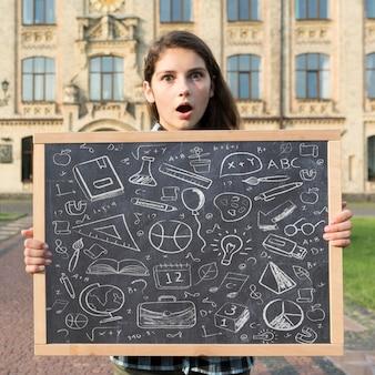 Удивленная девушка держит макет на доске