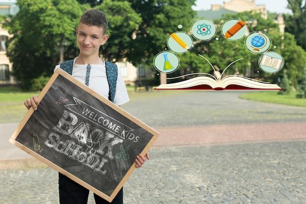 Мальчик держит макет на доске