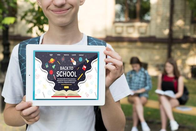 Улыбающийся мальчик держит макет планшета
