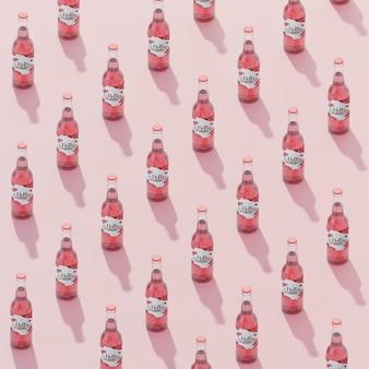 ピンクの背景と等尺性フルーツソーダの瓶