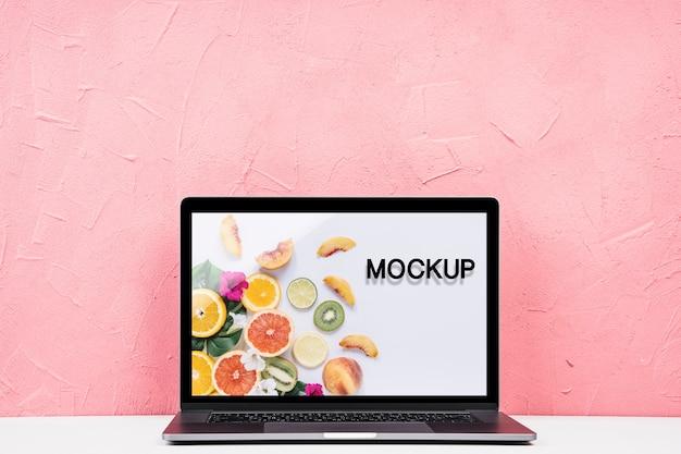 ピンクの背景を持つ正面モックアップノートパソコン