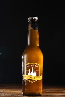 黒い背景と正面のビール瓶