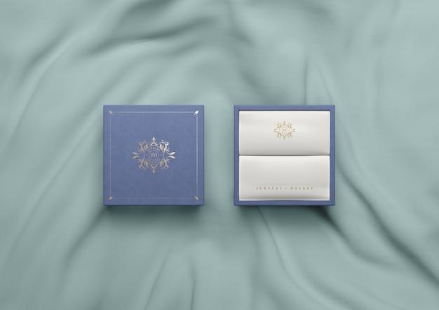 Вид сверху синяя коробка на шелковой ткани
