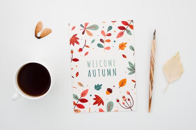 カードとコーヒーの横にある秋のカード