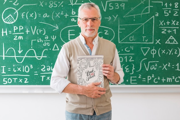 Учитель математики держит школьную тетрадь