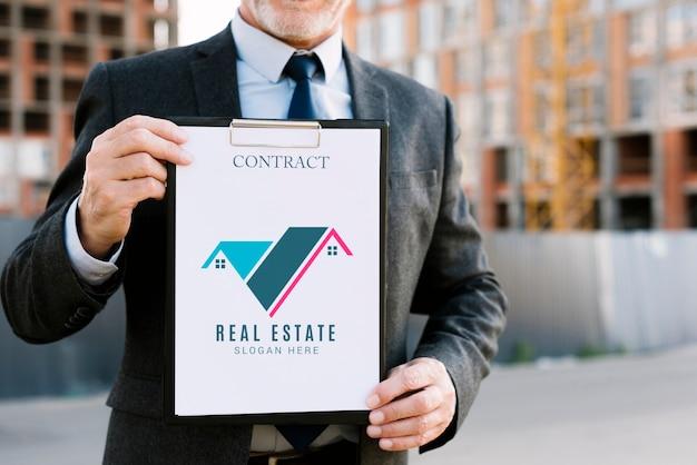 Мужчина держит макет буфера обмена для архитектурного бизнеса