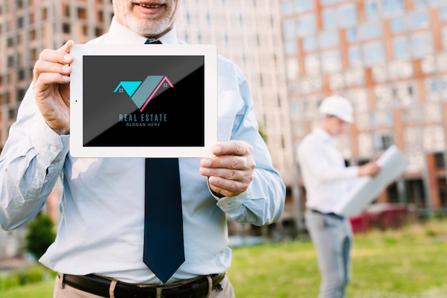 Архитектор держит макет планшета перед зданием