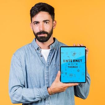 Вскользь молодой человек держит макет планшета