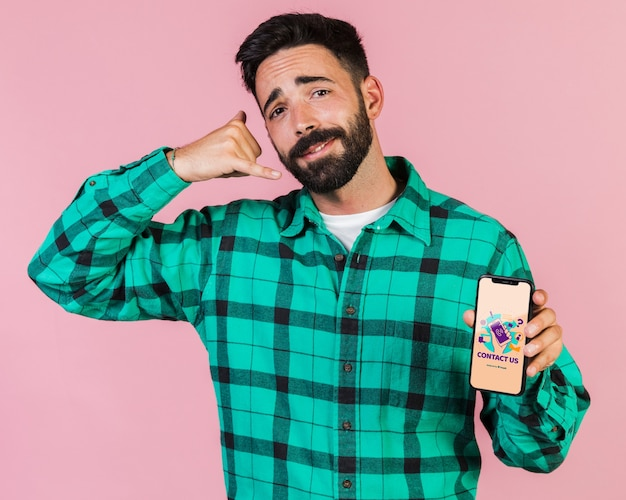 若い男が電話で話すふりをして携帯電話のモックアップを保持