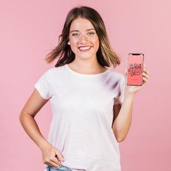 携帯電話のモックアップを保持している若い女性の笑みを浮かべてください。