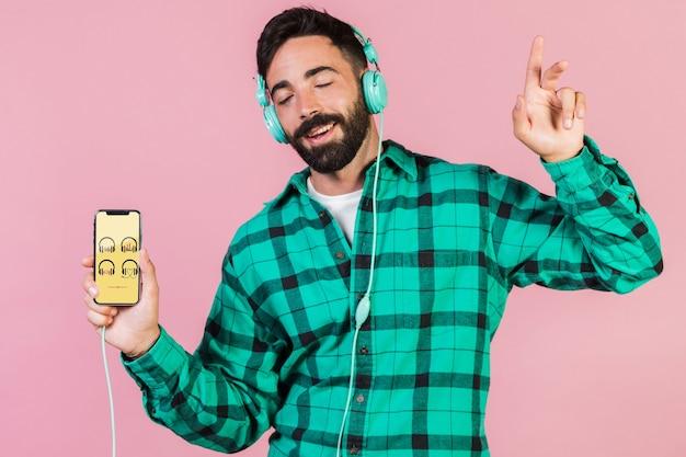ヘッドフォンと携帯電話のモックアップとうれしそうな若い男