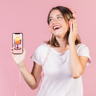 携帯電話のモックアップを保持しているヘッドフォンで若い女性を笑ってください。