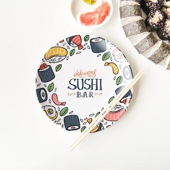 寿司プレートと白い背景の上の箸のフラットレイアウト