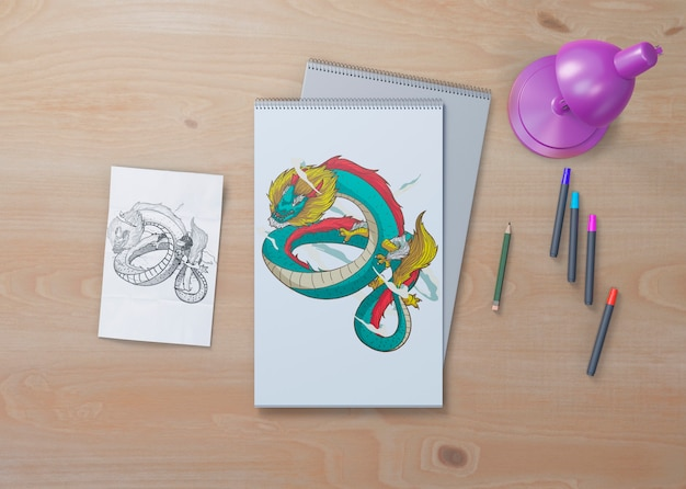 Эскиз змеи на белых листах на столе