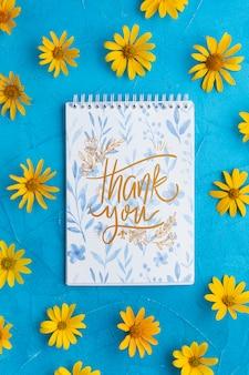 ノートブックと青色の背景に花のトップビュー