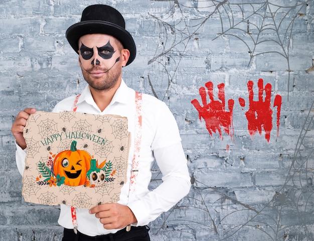 Мужчина с макияжем держит открытку с тыквой на хэллоуин