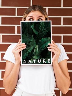 Женщина держит журнал и смотрит в сторону макет