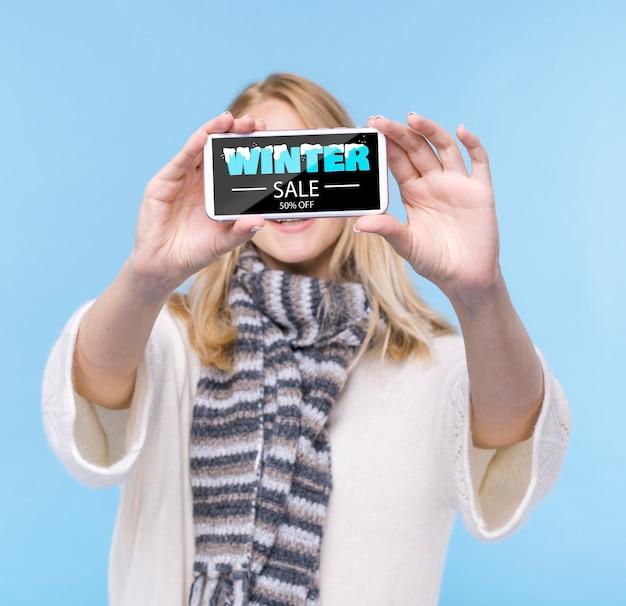 Молодая женщина держит телефон с макетом