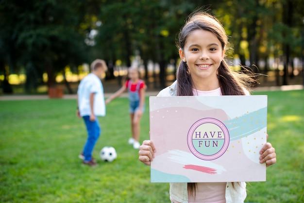 Молодая девушка в парке с табличкой с положительным сообщением