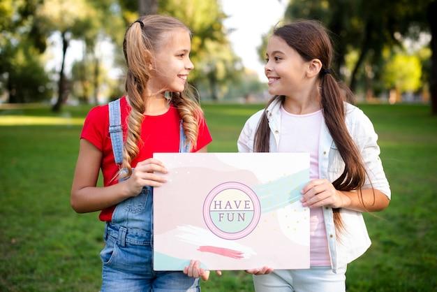 Девочки, держа вместе бумаги с мотивационным сообщением