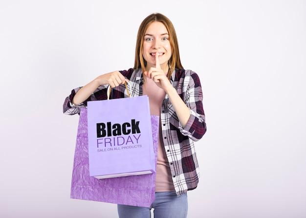 Женщина держит бумажные пакеты и делает знак тсс