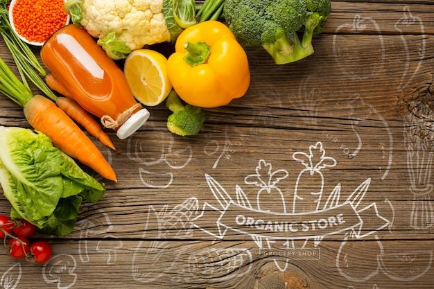 にんじんジュースと野菜の木製テーブル
