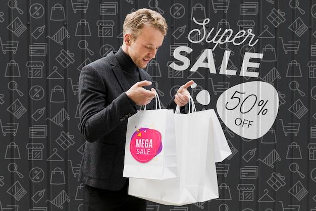 Удовлетворенный мужчина проверяет его покупки